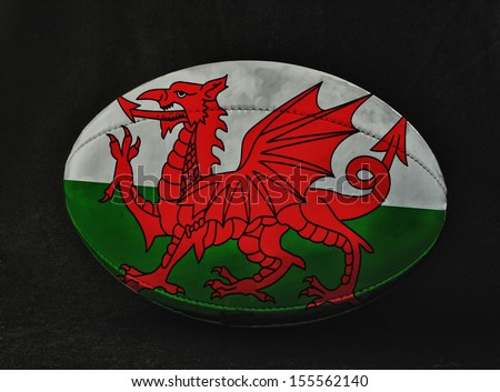 Rugby ball with Wales flag colors, over black background - stock photo