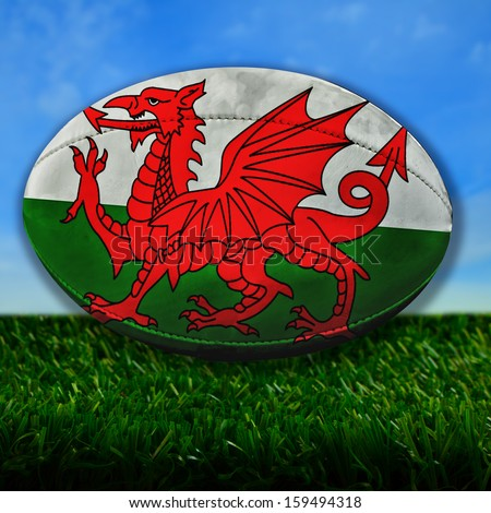 Rugby ball with Wales flag over grass - stock photo