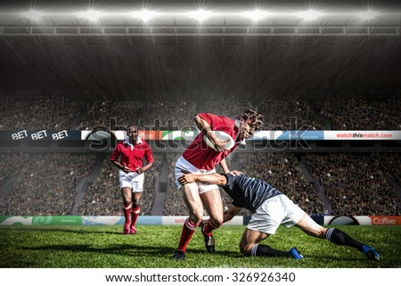 Rugby fans in arena against rugby players tackling during game - stock photo