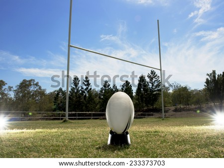 Rugby football in front of the goal posts, with lighting effects either side