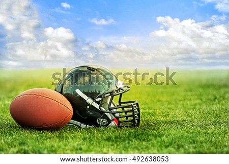Rugby helmet with ball on green grass and blue sky background