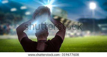 Rugby player about to throw a rugby ball against pitch and stands - stock photo