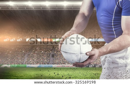 Rugby player about to throw the rugby ball against rugby fans in arena - stock photo