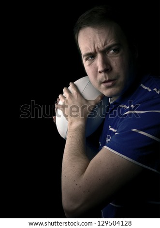 rugby player guarding ball on black background with copy space