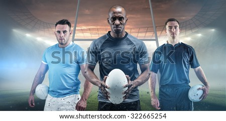 Rugby player holding a rugby ball against rugby stadium - stock photo