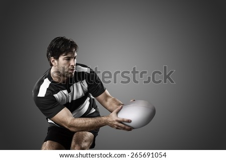 Rugby player in a black uniform on a black background. - stock photo