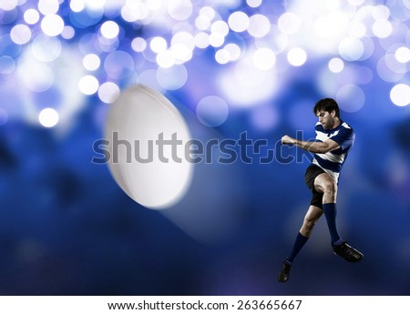 Rugby player in a blue uniform kicking a ball on a blue lights background.