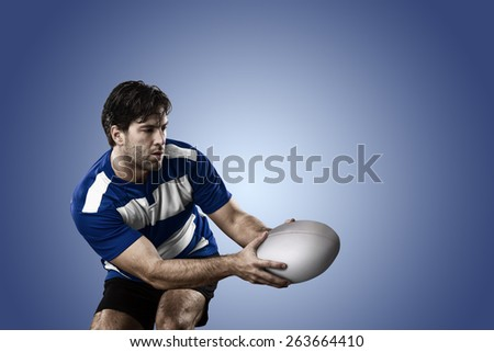 Rugby player in a blue uniform on a blue background. - stock photo