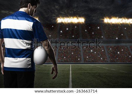 Rugby player in a blue uniform on a stadium. - stock photo