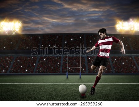 Rugby player in a red uniform kicking a ball on a stadium. - stock photo