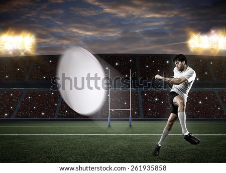 Rugby player in a white uniform kicking a ball on a stadium. - stock photo