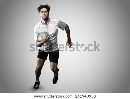 Rugby player in a white uniform running on a white background. - stock photo