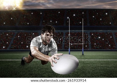 Rugby player in a white uniform scoring on a stadium. - stock photo