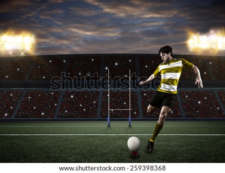Rugby player in a yellow uniform kicking a ball on a stadium. - stock photo