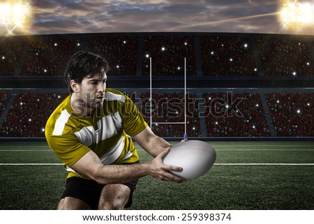 Rugby player in a yellow uniform on a stadium. - stock photo