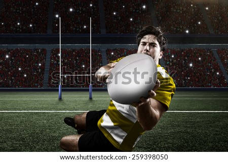 Rugby player in a yellow uniform scoring on a stadium. - stock photo
