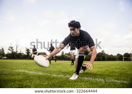 Rugby players training on pitch at the park - stock photo