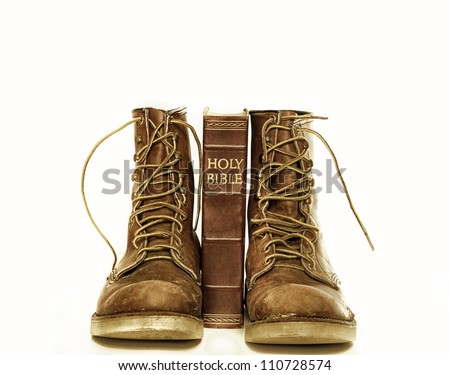 Rugged boots and bible isolated against white - stock photo
