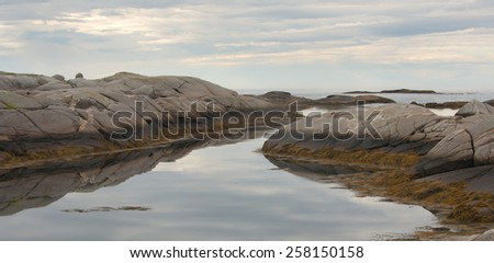 Rugged granite rock coastal image with cloudy sky. - stock photo