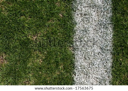 Rugged grass and yard line of a football field - stock photo