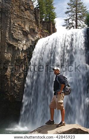 Rugged hiker views the wild terrain at Rainbow Falls in the Devils Postpile NM - stock photo