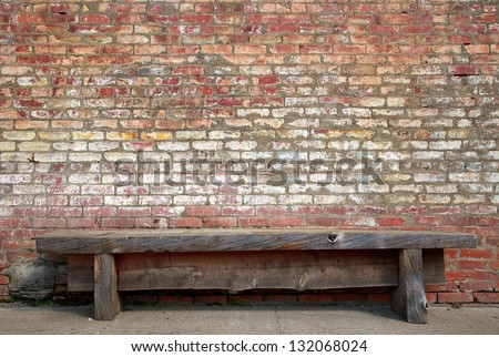 Rugged, primitive wooden sidewalk bench beside multi-colored very old brick wall background. - stock photo
