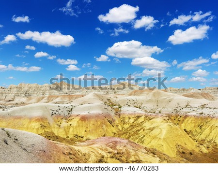 Rugged terrain in Badlands National Park, South Dakota, beneath blue sky and clouds. Horizontal shot.