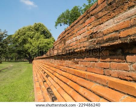Ruin and ancient orange brick wall of Ayuttaya with tree and sky background, Thailand - stock photo