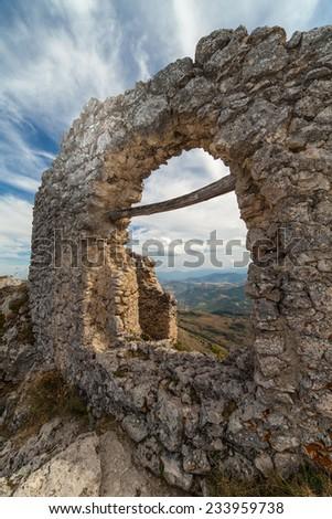 Ruin in the Rocca calascio castle under a blue sky with white clouds - stock photo