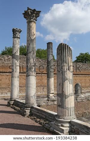 Ruin of ancient corinthian columns in Hadrian's Villa (Villa Adriana in Italian) is a large Roman archaeological complex at Tivoli, Italy - stock photo