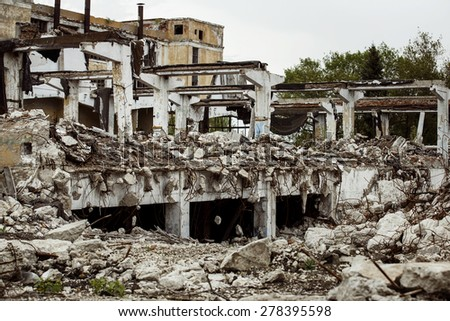Ruined building of a factory with concrete hanging on armature. Concept of disaster, war - stock photo