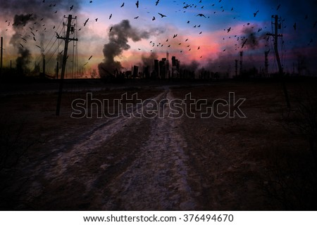 ruined city in smoke on a sunset background - stock photo