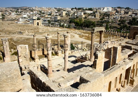 Ruins against Back Drop of City, at Roman City of Jerash, Jordan - stock photo