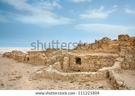 Ruins of a fortress of Masada with the Dead Sea look through in the distance - stock photo