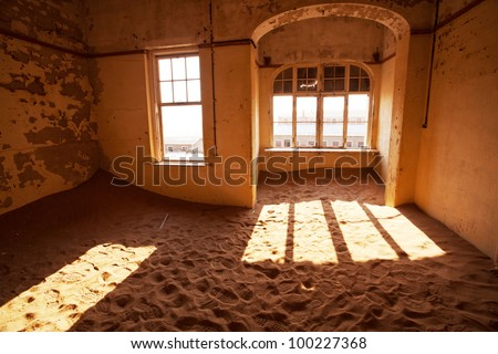 Ruins of abandoned houses in the ghost diamond town Kolmanskop, Namibia, Africa in storm - stock photo