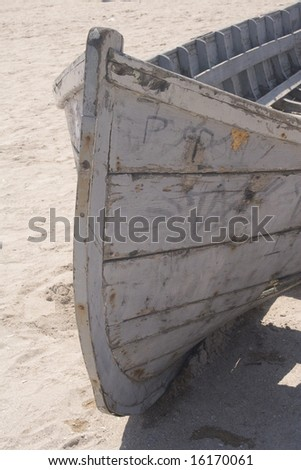 Ruins of an old fishing boat on sand - stock photo