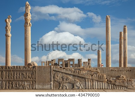 Ruins of Apadana and Tachara Palace behind stairway with bas relief carvings in Persepolis UNESCO World Heritage Site against cloudy blue sky in Shiraz city of Iran. - stock photo