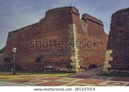 Ruins of brick fortification walls and cobblestone alleys of the medieval strategic fortress of Alba Iulia, Romania. - stock photo
