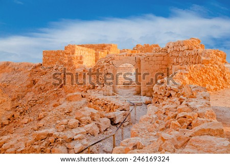 Ruins of Massada Fortress in Negev at sunset - stock photo