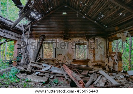 Ruins of old abandoned wooden house. Destroyed room with windows. - stock photo