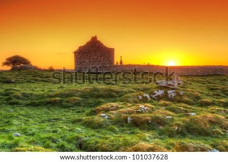 Ruins of old Irish chapel in Burren at sunrise - stock photo