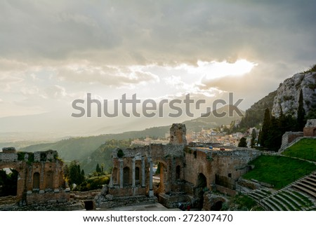 Ruins of the ancient greek theater of Taormina, Sicily the Etna with its double snook tail in the background above the morning sun lit Giardini-Naxos bay - stock photo