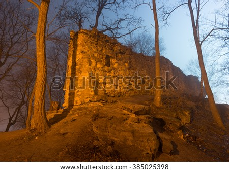 Ruins of the castle in foggy night forest. Lviv High Castle - stock photo
