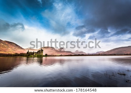 Ruins of the castle on the lake in winter - stock photo