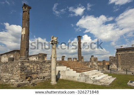 Ruins of the Temple of Jupiter, Capitolium, or Temple of the Capitoline Triad in roman Pompeii, with sundial on the column in foreground, Italy - stock photo