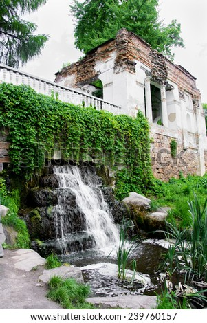 Ruins with waterfall in summer park