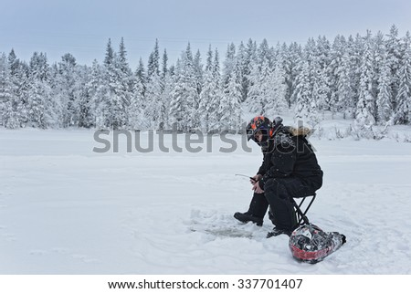 RUKA, FINLAND, JANUARY 7, 2013: Man is ice-fishing in Ruka in Lapland, Finland