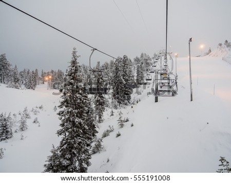 RUKA, FINLAND - JANUARY 2017: Ski lift with seats going over the mountain and paths from skies and snowboards. Ski resort, snow, extreme vacation, active holidays.