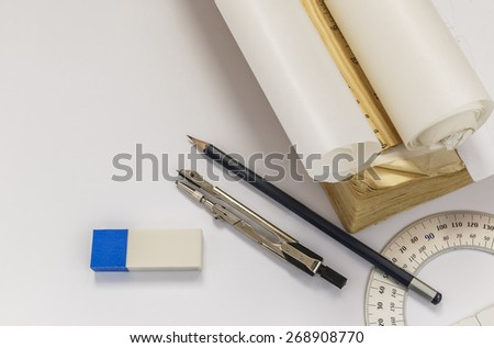 Ruler, compasses, eraser, protractor, pencil and tracing paper roll - stock photo