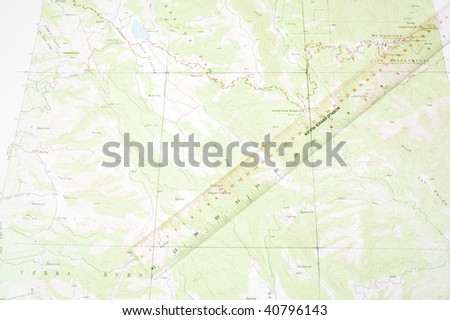 ruler laying on a topographical map to do distance measurement with - stock photo